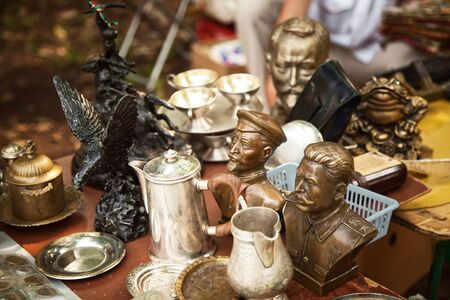USSR famous historic persons busts and metal tableware at a flea market. Many old vintage things at a garage sale 版權商用圖片