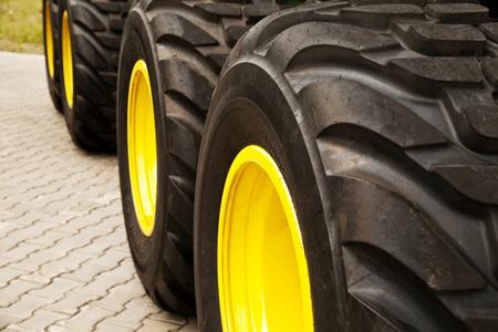 Row of big yellow truck wheels background. Huge industrial tractor  tires