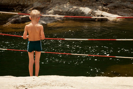 Little boy standing alone by a warning fence at the bank of a river looking at the water in summer. Unattended Caucasian kid in swimming trunks in a dangerous situation by deep water