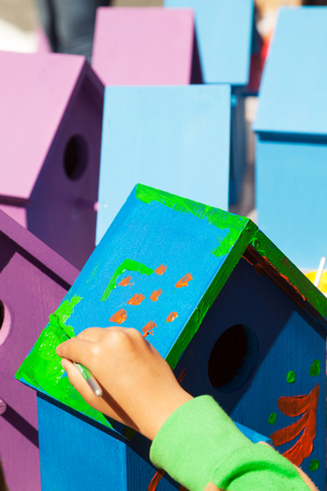 Child hand painting a birdhouse bright colors of blue and purple. Kids woodcraft lesson, making wooden houses for birds