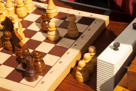 Wooden chess pieces on a chessboard next to a clock during a match. Strategy board game process