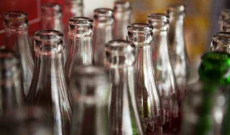 Many used glass bottles arranged in rows for recycling. Open empty soda bottles background