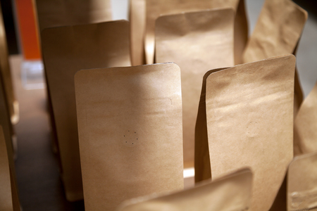 Group of brown kraft paper bags with air vent close-up. Blank retail coffee packaging with copy space