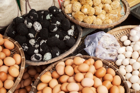 Several baskets of raw and cooked eggs at Vietnamese market. Pile of Asian delicacy black century eggs in ash Stockfoto