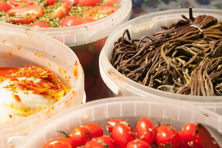 Various pickled salads at a Russian food market stall. Different marinated vegetables in buckets for sale - fern, tomatoes, cabbage Stockfoto