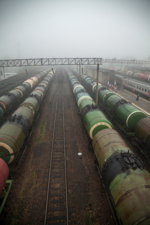 Several lines of of tank cars at a railway station in a fog. Depressive industrial Russian landscape with a lot of freight trains