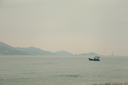 Misty gray seascape with a Vietnamese fishing boat. Fishermen in the sea bay in the morning. Beautiful mountains and ocean landscape background with copy space