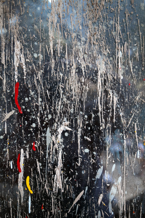 Abstract paint splash on a gray wall. Red and yellow stains on a messy dirty background