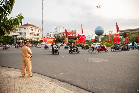 Nha Trang, Vietnam - March 30, 2018: Vietnamese traffic police officer controlling motorbikes flow. Asian male policemen wearing tan uniform regulates the city road transport Banco de Imagens - 113516634
