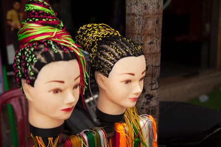Street hairdresser salon offering braids hairstyle service. Two women heads dummies demonstrating hairdos with colorful strings Stockfoto - 113569009