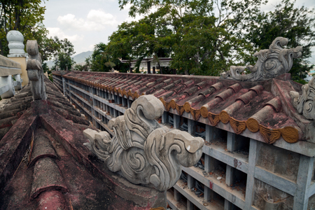 Destroyed traditional Buddhist columbarium in Vietnam. Beautiful decorated Asian cinerary cemetery with empty niches Stockfoto - 113569010