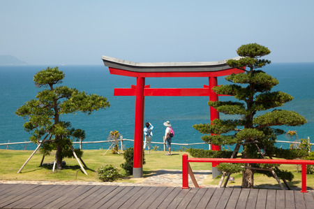 Beautiful landscape with red Japanese religious gate in a park on a seashore. Couple of tourist looking at view near the Buddhist torii Stockfoto
