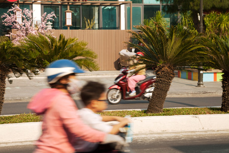 Two motorbikes in motion on a quiet sunny road. Blurry mother and a child on riding a bike on an Idyllic tropical city street with palm trees Stockfoto