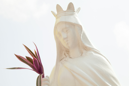 Old white sculpture of a saint woman wearing a crown and holding a bouquet. Catholic holy vintage statue against the light sky Stockfoto