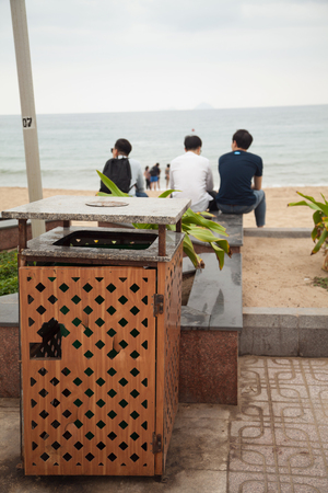Three Young Asian man looking at the sea view. 3 people from behind sitting on a city beach near a trash bin. Focus on a trash can Stockfoto - 113569025