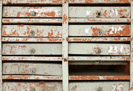 Block of very old damaged mailboxes in an apartment building. Many vintage painted postboxes in a row vintage background