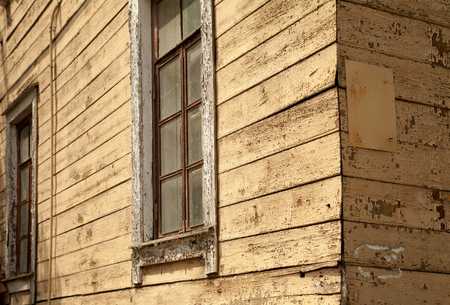 Old shabby beige wooden house close-up background. Weathered walls, corner and windows of a rustic shack Stockfoto