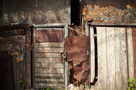 Old weathered wooden shed wall textured background. Rustic damaged wood barn with a closed door at a slum Stockfoto