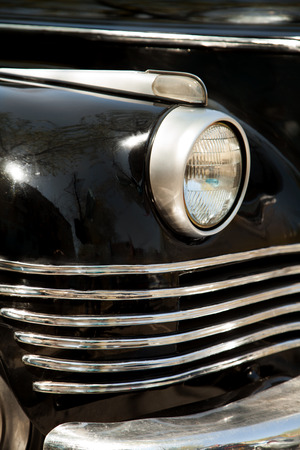 Soviet black retro car ZIS front close-up. A headlight and a radiator grille detail of a vintage USSR auto Stockfoto
