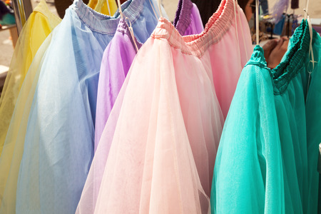 Row of hanging colorful gauze skirts at a clothing store. Brightly colored performance costumes background Stockfoto - 113569049
