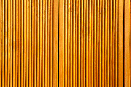 Yellow wooden wall panels decorated with vertical grooves. Abstract geometrical carved wood background Stockfoto - 113569058