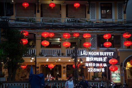 Nha Trang, Vietnam - March 31, 2018: Asian restaurant exterior decorated with red paper lanterns. People eating at a Chinese buffet, view of windows from outside. Text in Chinese: Chongqing Duck Intestine King,  seafood hot pot buffet