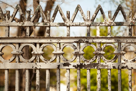 Old peeled metal fence in a garden out of focus. Colorful background with geometric pattern ornament Stockfoto