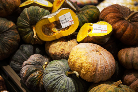 Pile of pumpkins with price tags at a supermarket. Many green and brown vegetables whole and cut in halves background