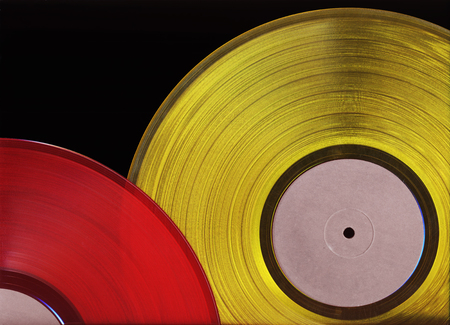 Two colored vinyl records isolated on black background. Retro music discs of red and yellow colors close-up