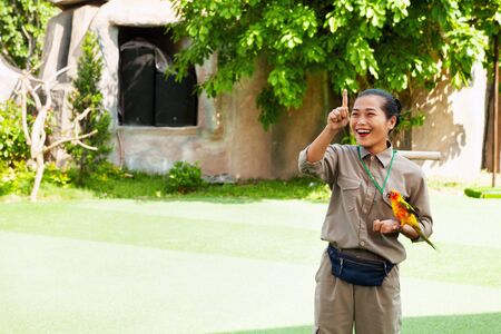 Nha Trang, Vietnam - April 4, 2018: Bird show at Vinpearl amusement park. Bird trainer holding a Sun Parakeet. Young Asian woman holding a colorful parrot on her hand and giving a gesture command