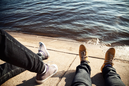 Legs of two friends hanging out together near the water. 2 young people sitting and relaxing on a bank of a river