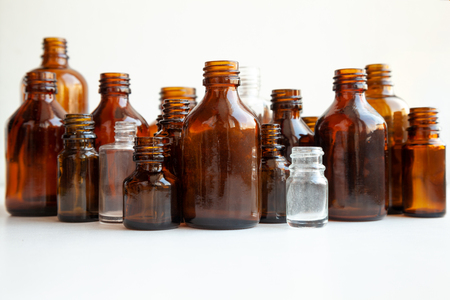 Group of various medical vials isolated on white. Many small brown bottles without labels