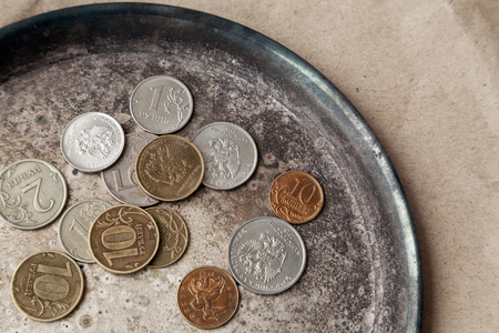 Some Russian coins scattered on a metal dish close-up. Various money of Russia with the eagle top view