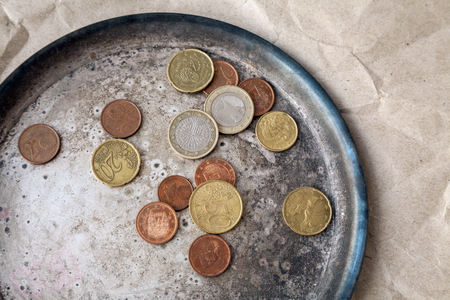 Some euro coins scattered on a metal dish close-up. Various money of  the European Union from above Stock Photo