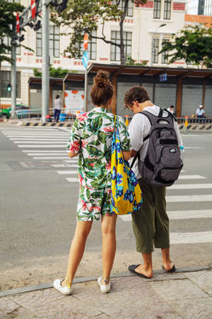 Ho Chi Minh City, Vietnam - August 18, 2019: Young couple of tourists on a crosswalk from behind. A man and a woman wearing casual summer clothes travel in Asia