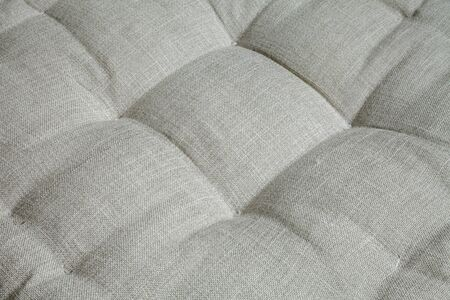 Gray upholstered furniture textile background. Soft, comfortable armchair seat close-up Stockfoto