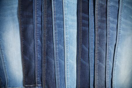 Many blue jeans arranged in a row background. Choice of casual pants at a clothing store