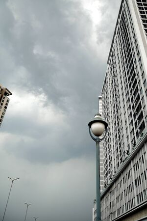 Tall gray buildings and lanterns in a city business district. Dull depressing city view on a cloudy day. Architectural background with copy space