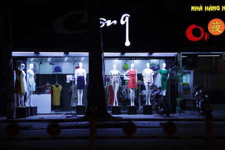 Ho Chi Minh City, Vietnam - May 8, 2020: Women's dresses displayed on dummies in front of a fashion store. Young Asian saleslady alone in a clothing boutique at night Redactioneel