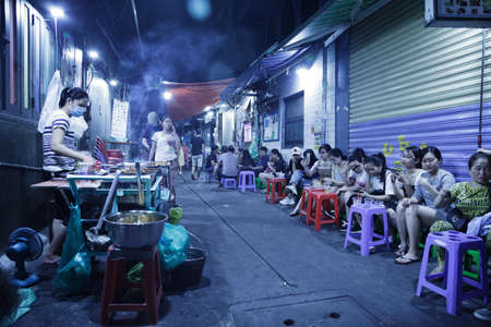 Ho Chi Minh City, Vietnam - May 8, 2020: Street food cafe cooking and serving cheap drinks and meat in a small lane. Asian women sitting in a row, drinking beer outdoors and looking at their phones. Vietnam night life Redactioneel