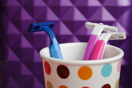 Three disposable pink and blue razors in a cup on a bathroom shelf. Colorful women and men hair removal accessories. Throuple relationship concept, living together Stockfoto
