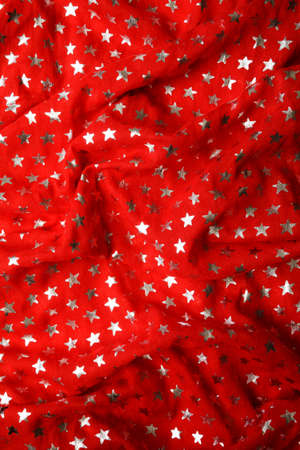 Silver stars pattern on red crumpled fabric. Festive colorful textured background
