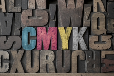letterpress words: The Letters CMYK written out in very old and worn letterpress type