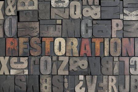 The word Restoration written in very old letterpress type