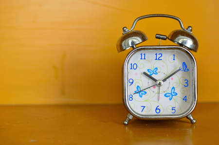 alarm clock and orange background photo
