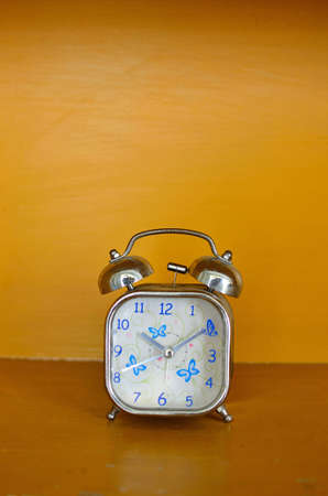 alarm clock and orange background Stock Photo - 12516308