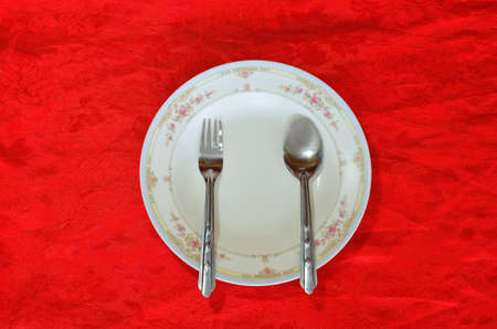 christmas dish: spoon and fork with white plate on red tablecloth Stock Photo