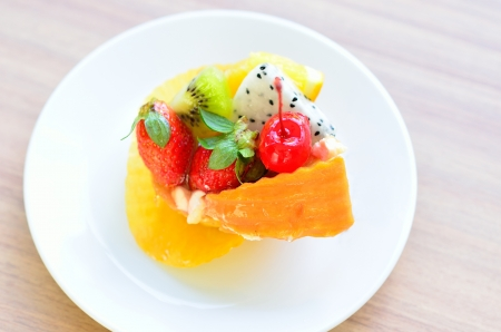 sweet cake with fruits on plate on wooden table photo