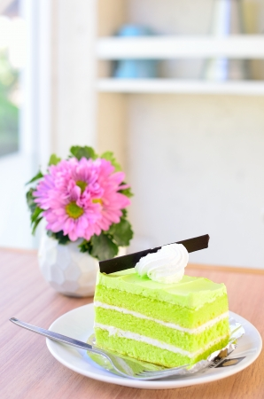 Sweet cake and flower on table photo