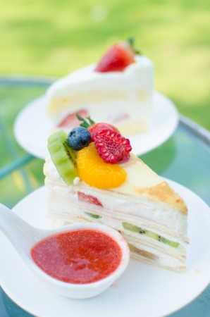 sweet cake with fruits on plate and green background photo